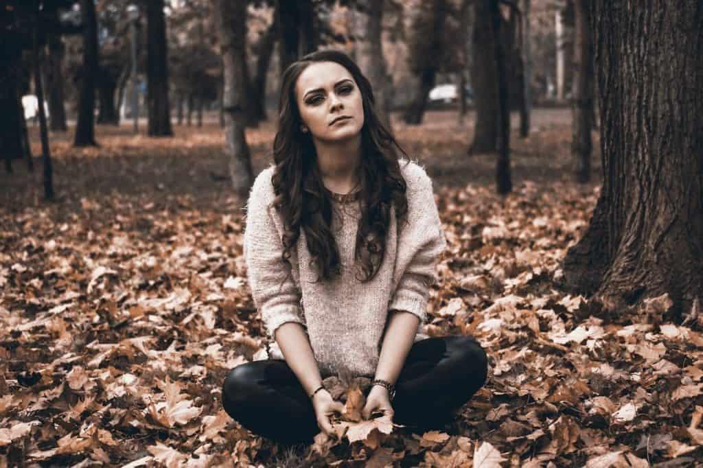 בחורה יושבת ביער לבדה