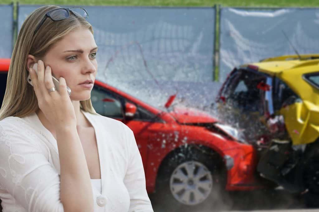 אישה מתקשרת בנייד על רקע מכוניות שעברו התנגשות